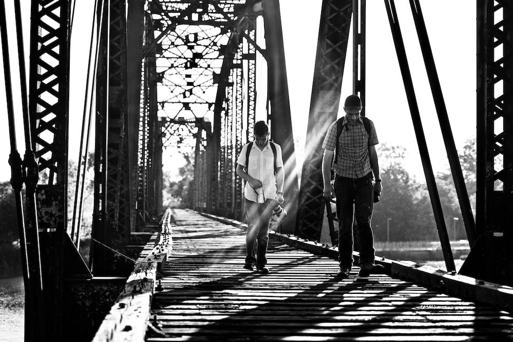 grayscale photography of two men on bridge