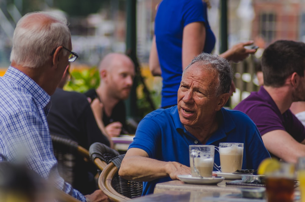man in blue polo shirt talking to man while drinking coffee