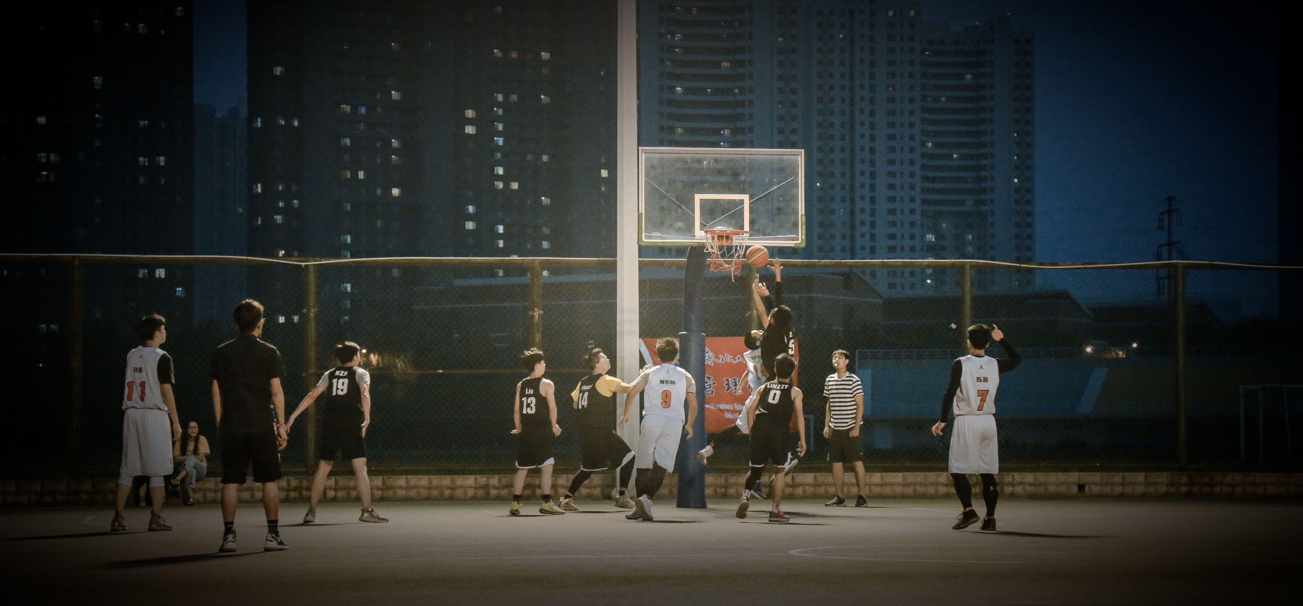 group of men playing basketball during nighttime