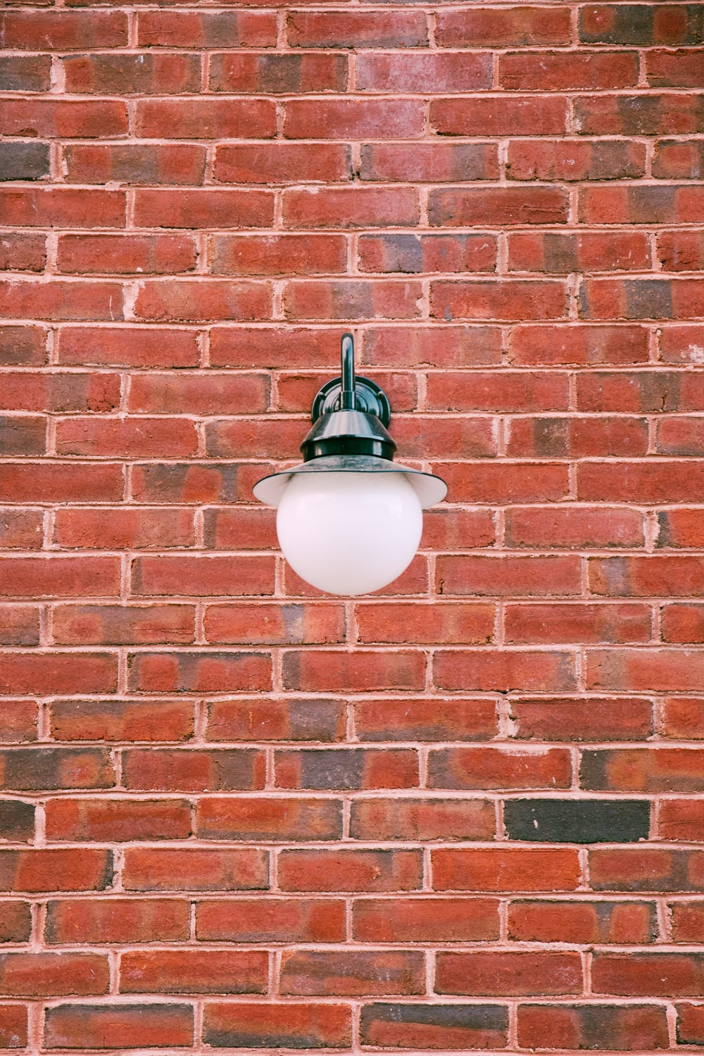turned-off outdoor light on red bricked wall