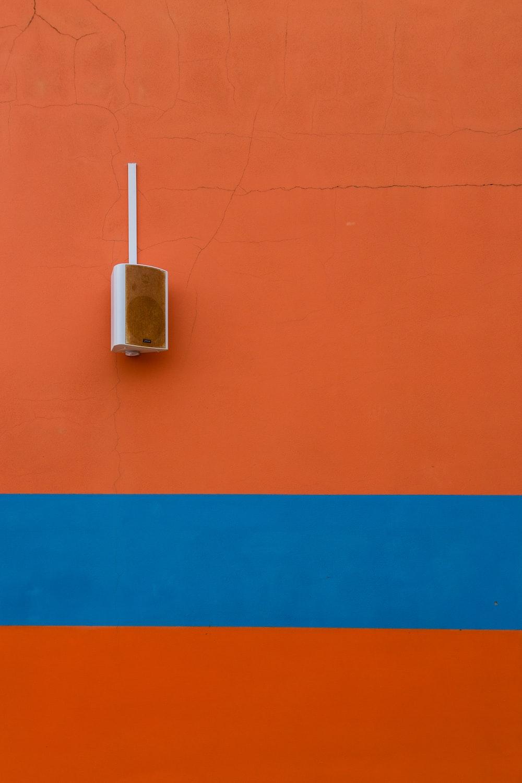 white speaker mounted on orange painted wall