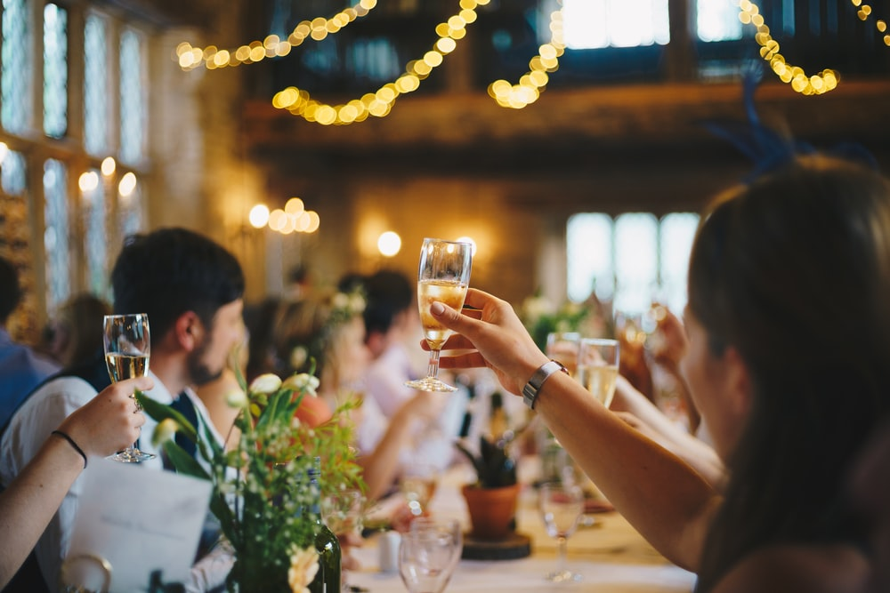 people raising wine glass in selective focus photography