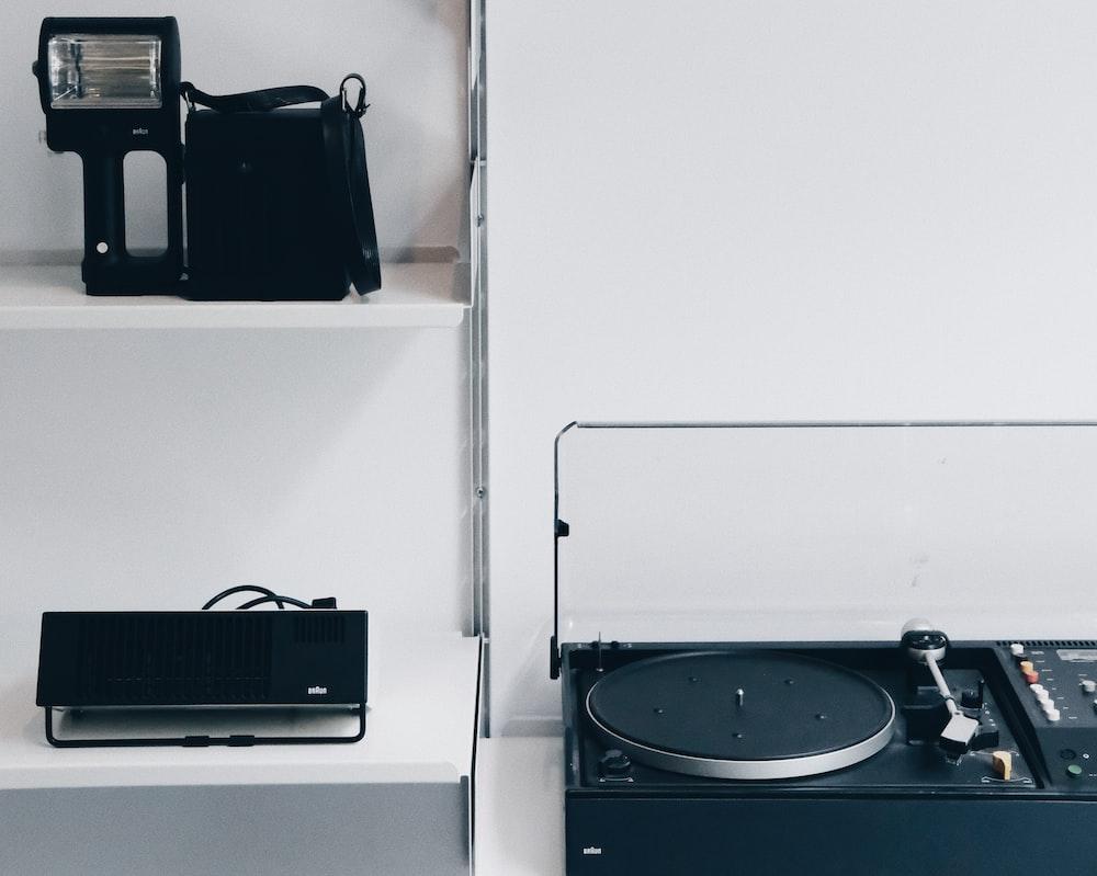 black portable turntable beside black laptop under black camera