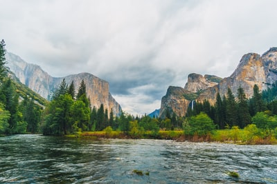 rippling of body of water surrounded by land formation yosemite teams background