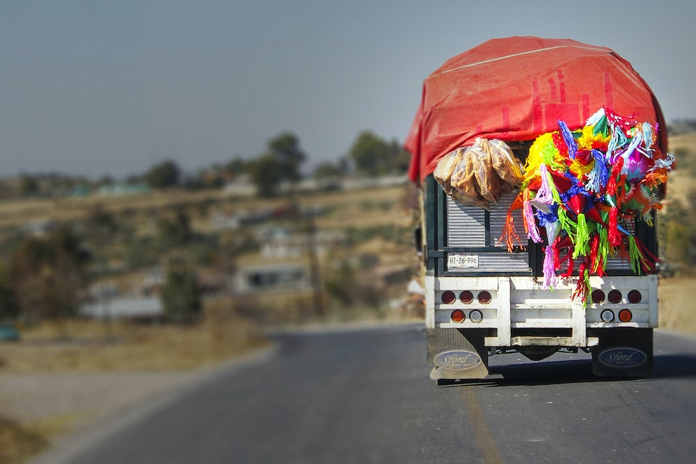 selective focus photography of truck carrying party hats