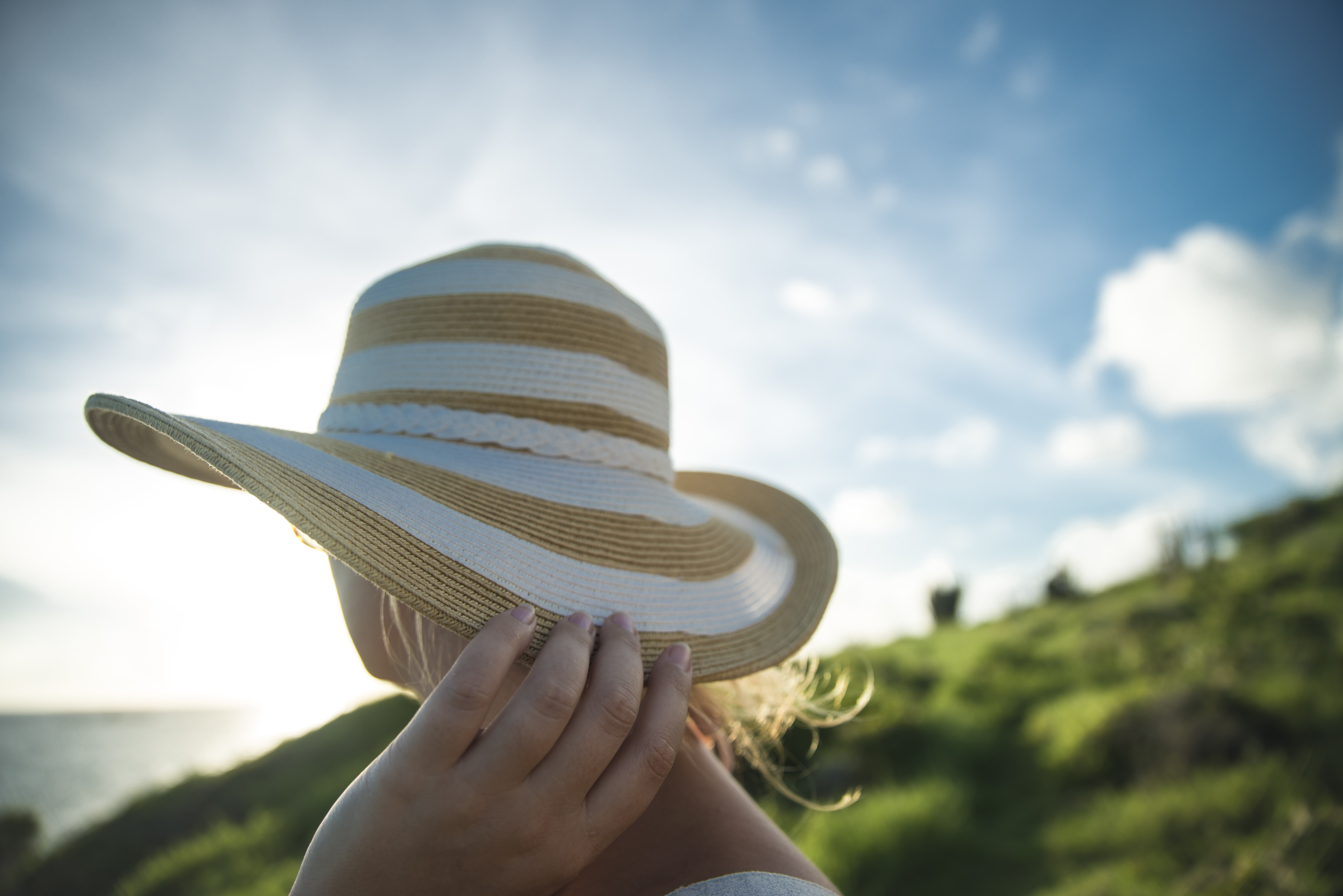 woman holding beige and gray sun hat