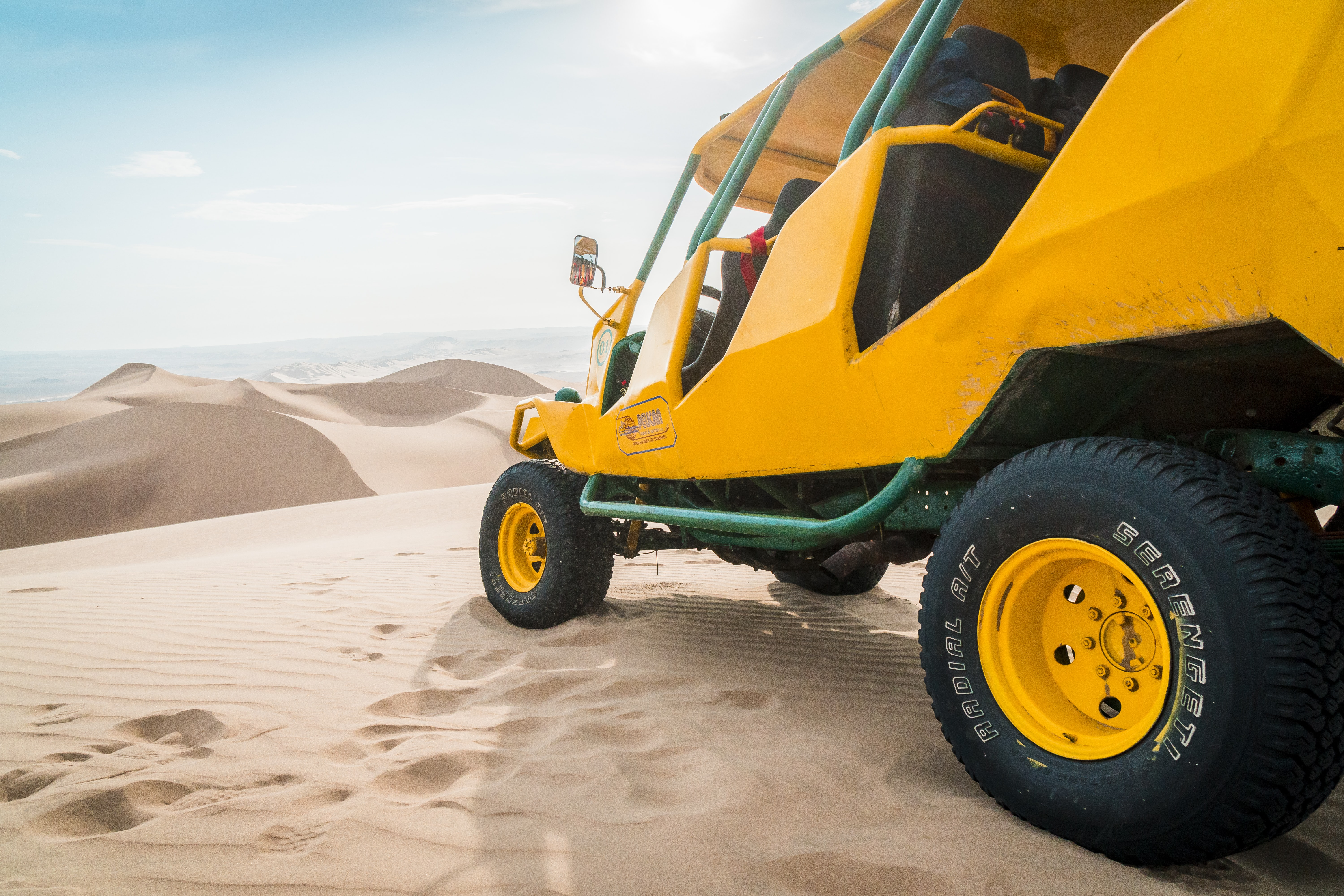 yellow and green UTV parked on a desert field