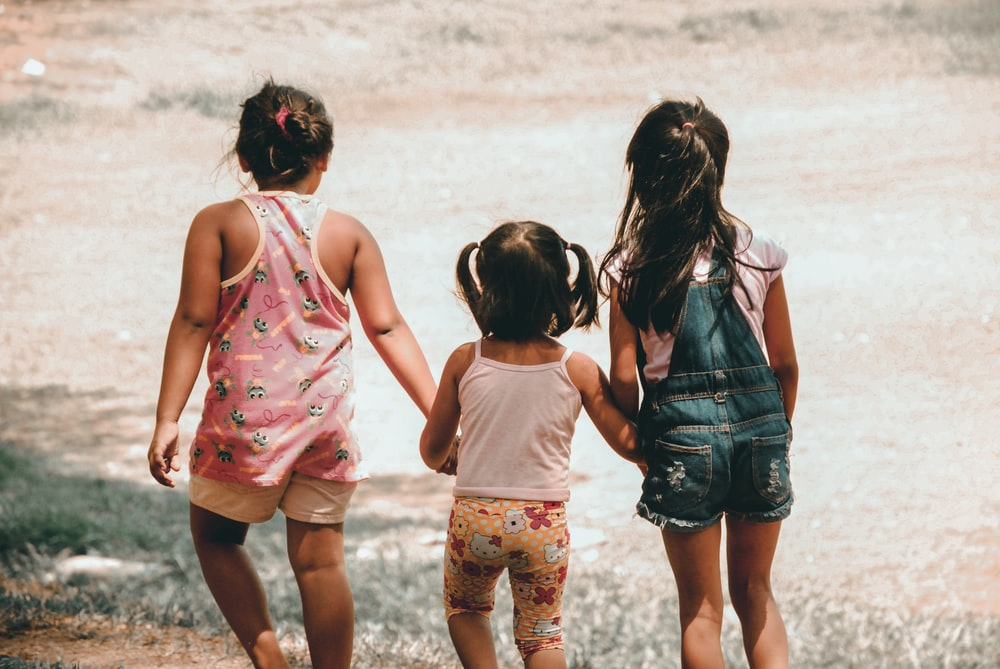 three girls holding each other hand walking towards brown soil