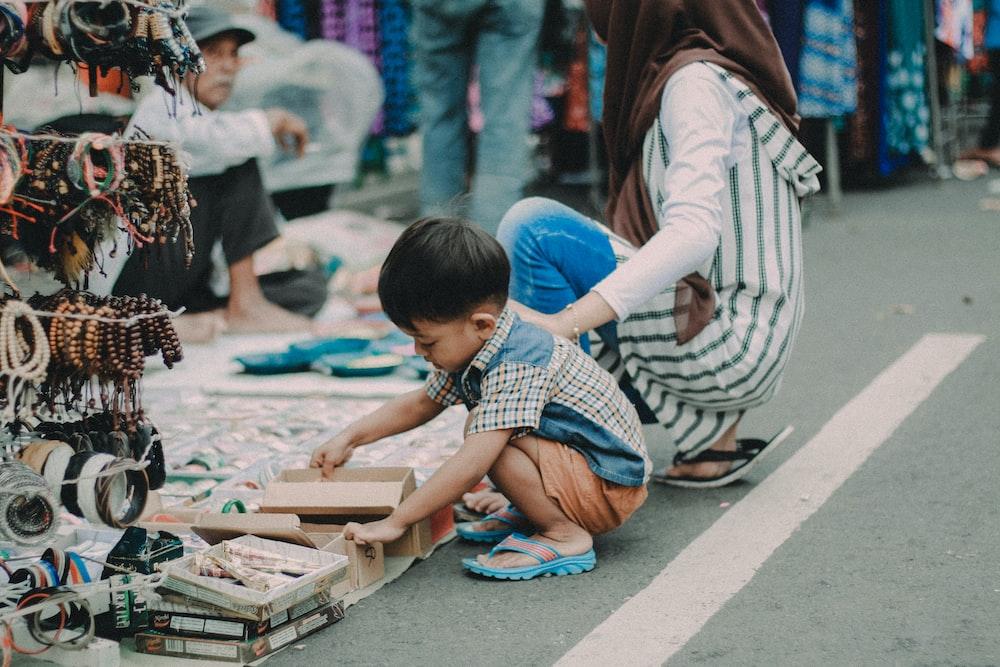 child doing asian squat on asphalt road