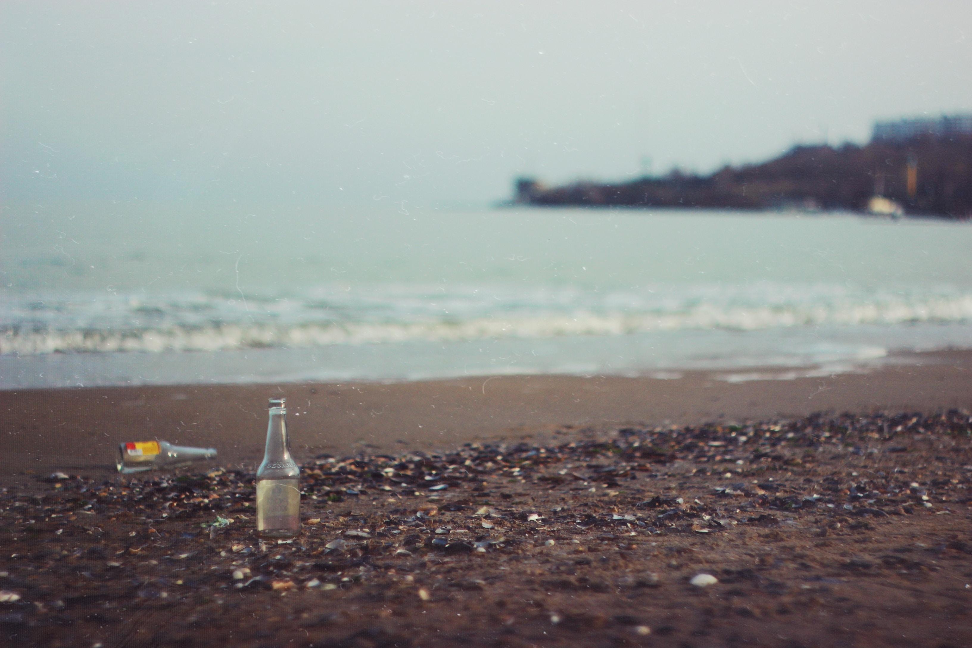 clear glass bottle on beach