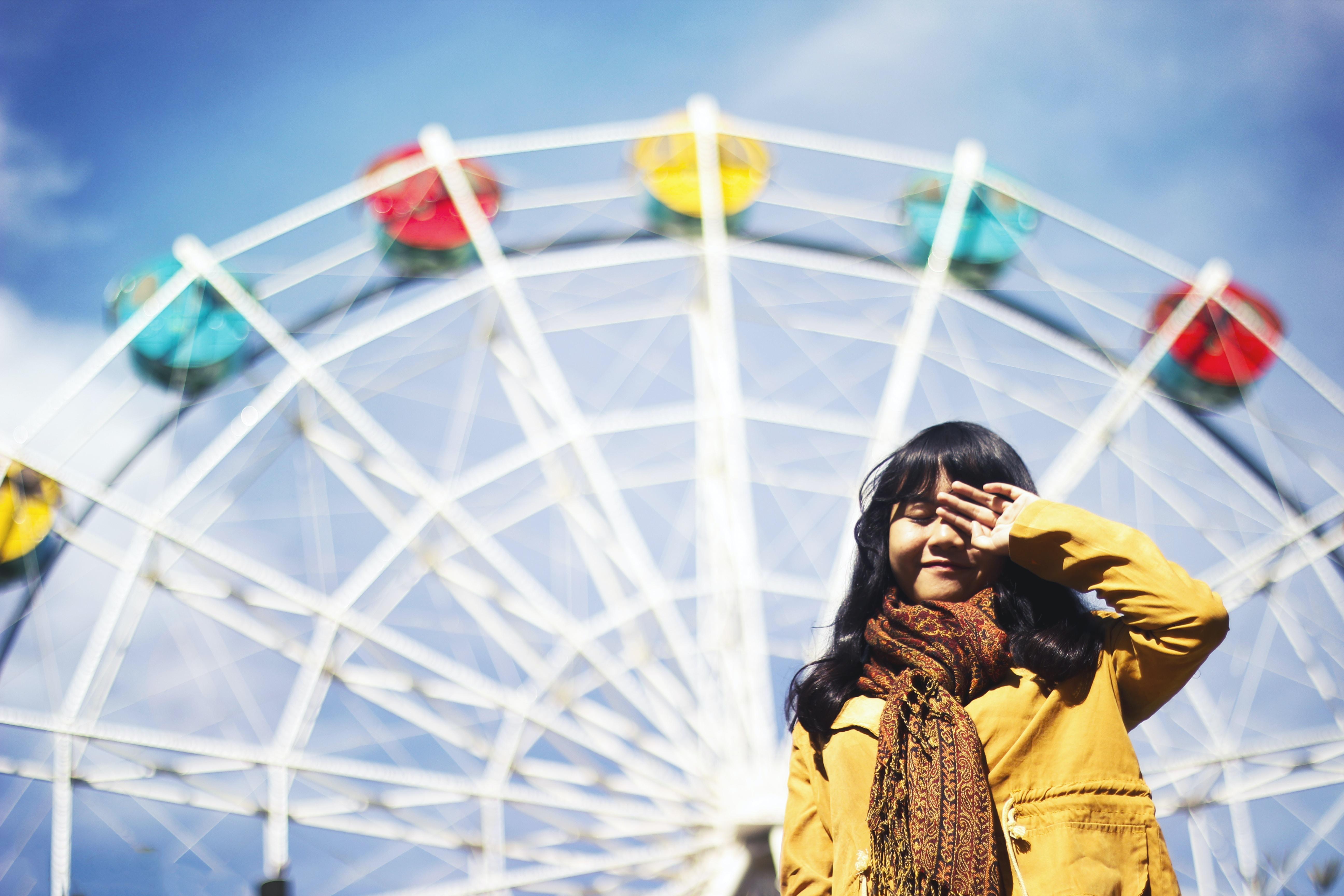 selective focus photo of woman closing left eye near Ferris wheel