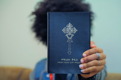 person holding blue book