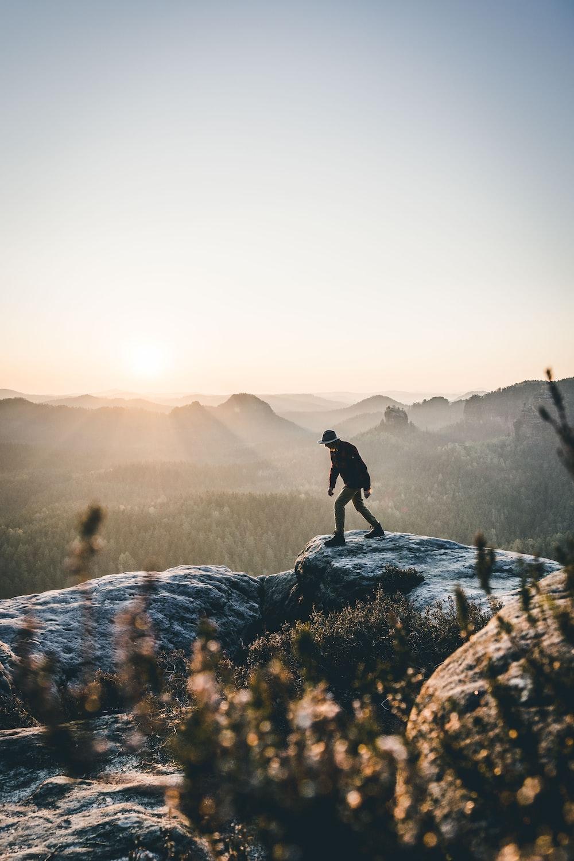 man walking on gray rock mountain during daytime