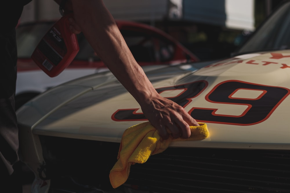 closeup photo of person wiping white racing card
