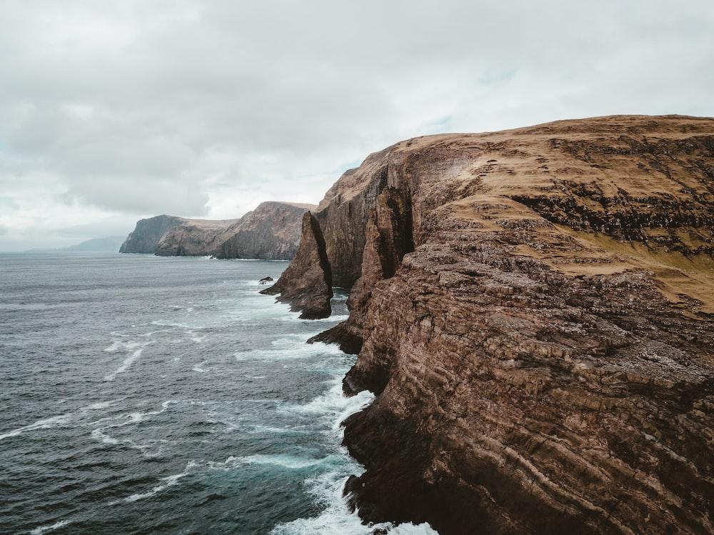 brown rock formation under grey clouds