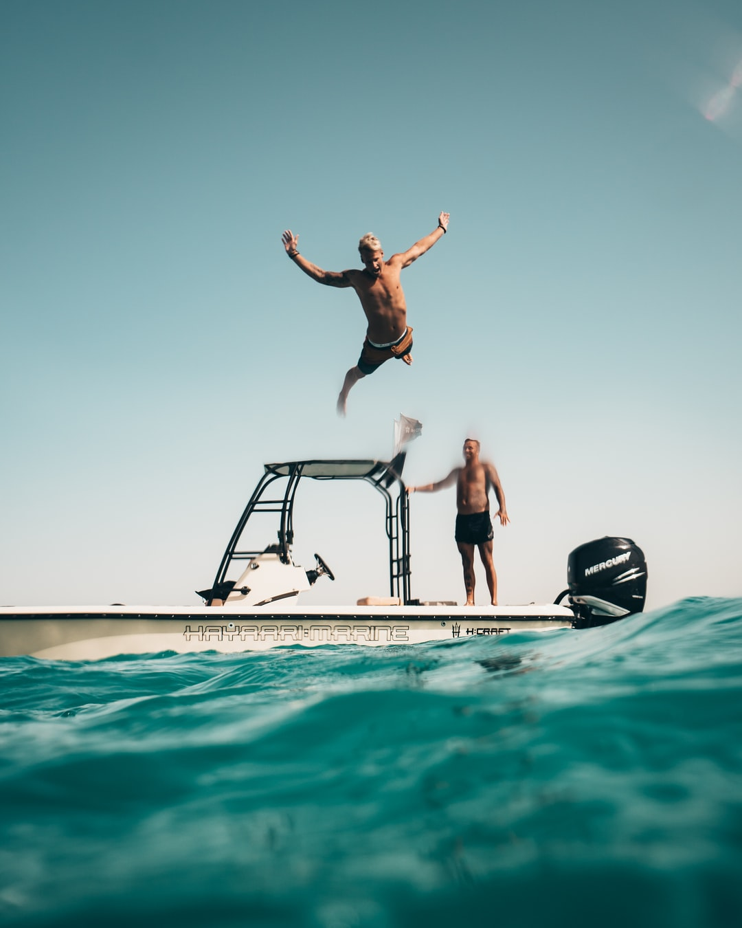 Friends having fun, jumping of boat into the ocean in Abu Dhabi.