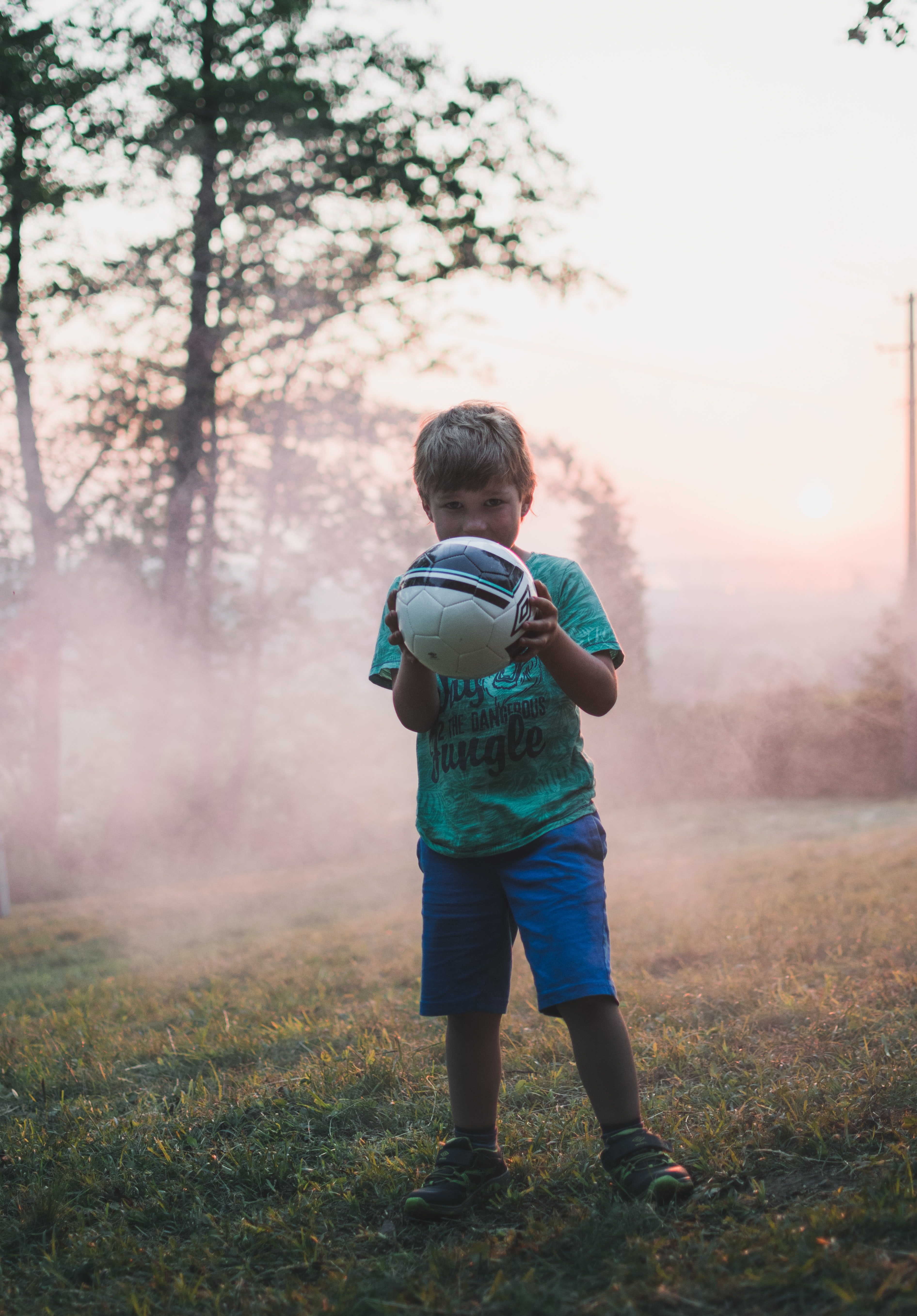 shallow focus photography of boy holding a ball