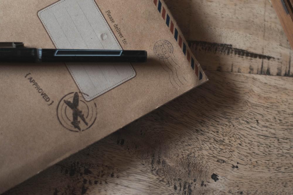 closeup photo of black ballpoint pen on book
