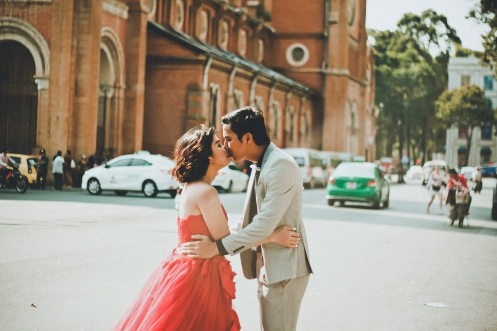 couple kissing on street near building during daytime