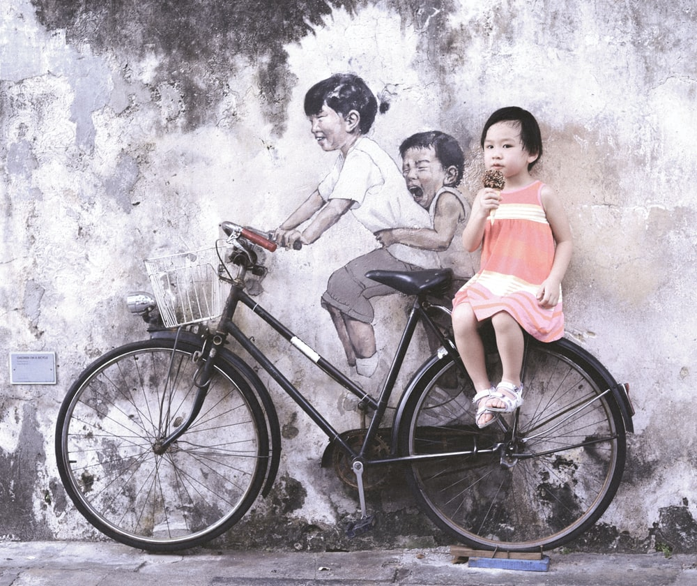 girl wearing orange and white sleeveless dress eating ice cream while sitting on black and white bike leaning on wall