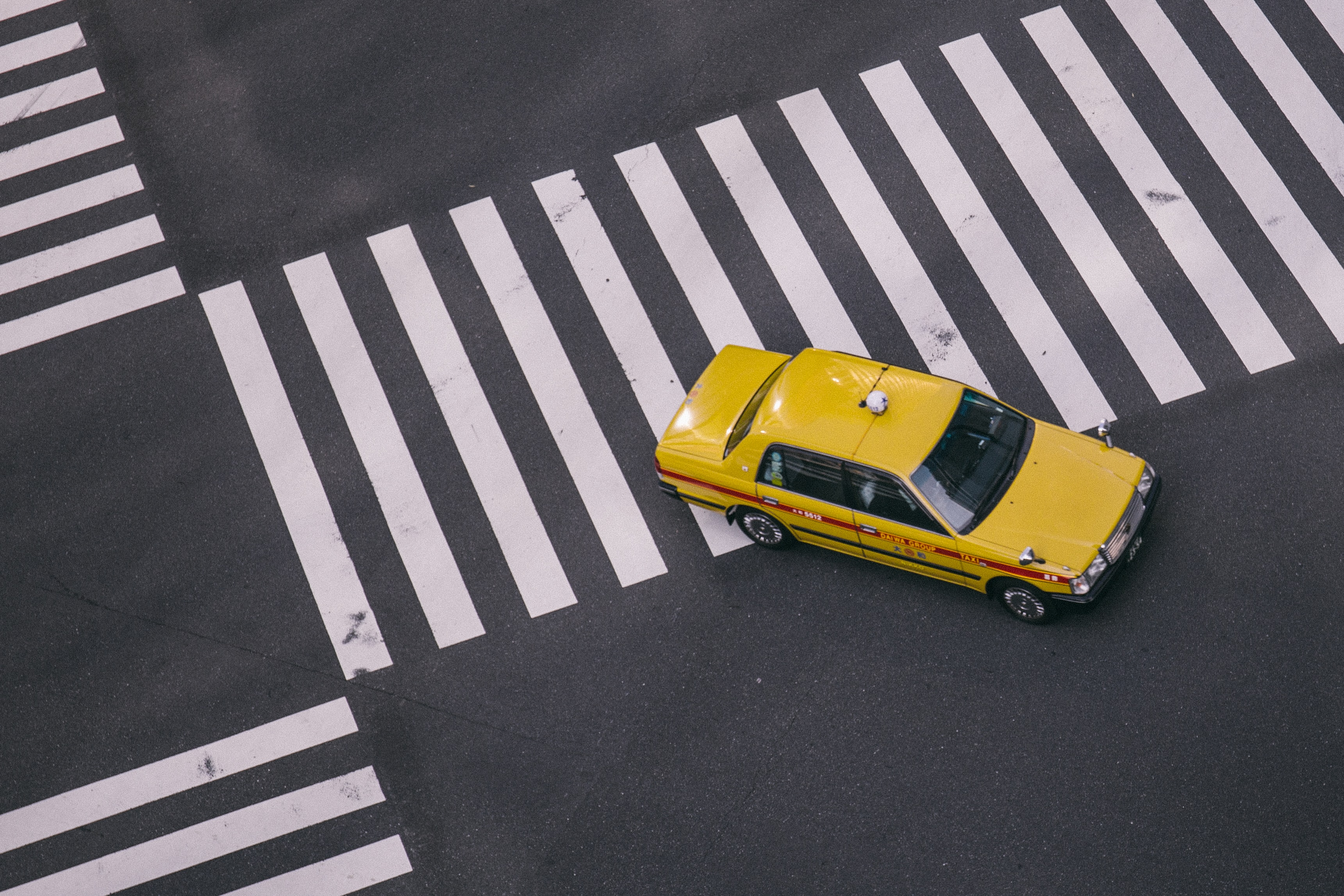 yellow taxi on gray pave road during daytime