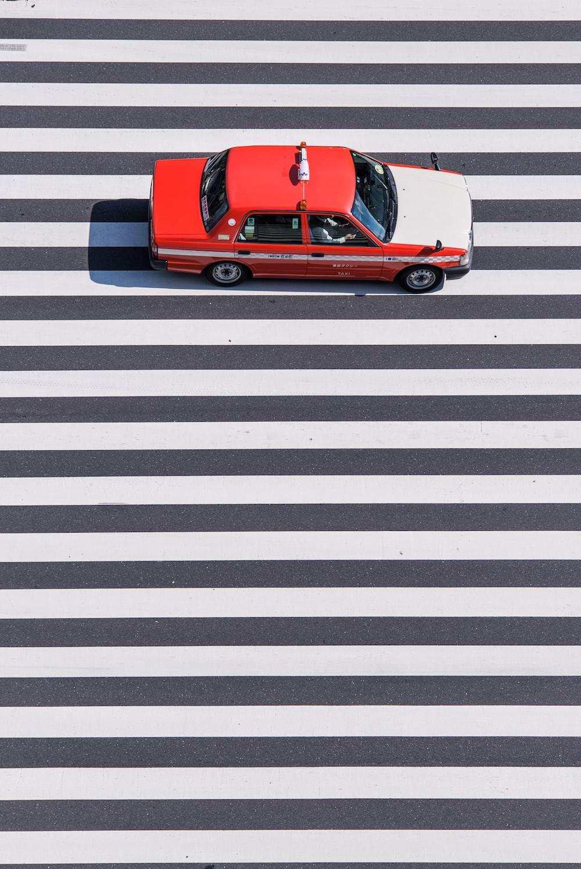 red and white sedan passing on pedestrian lane