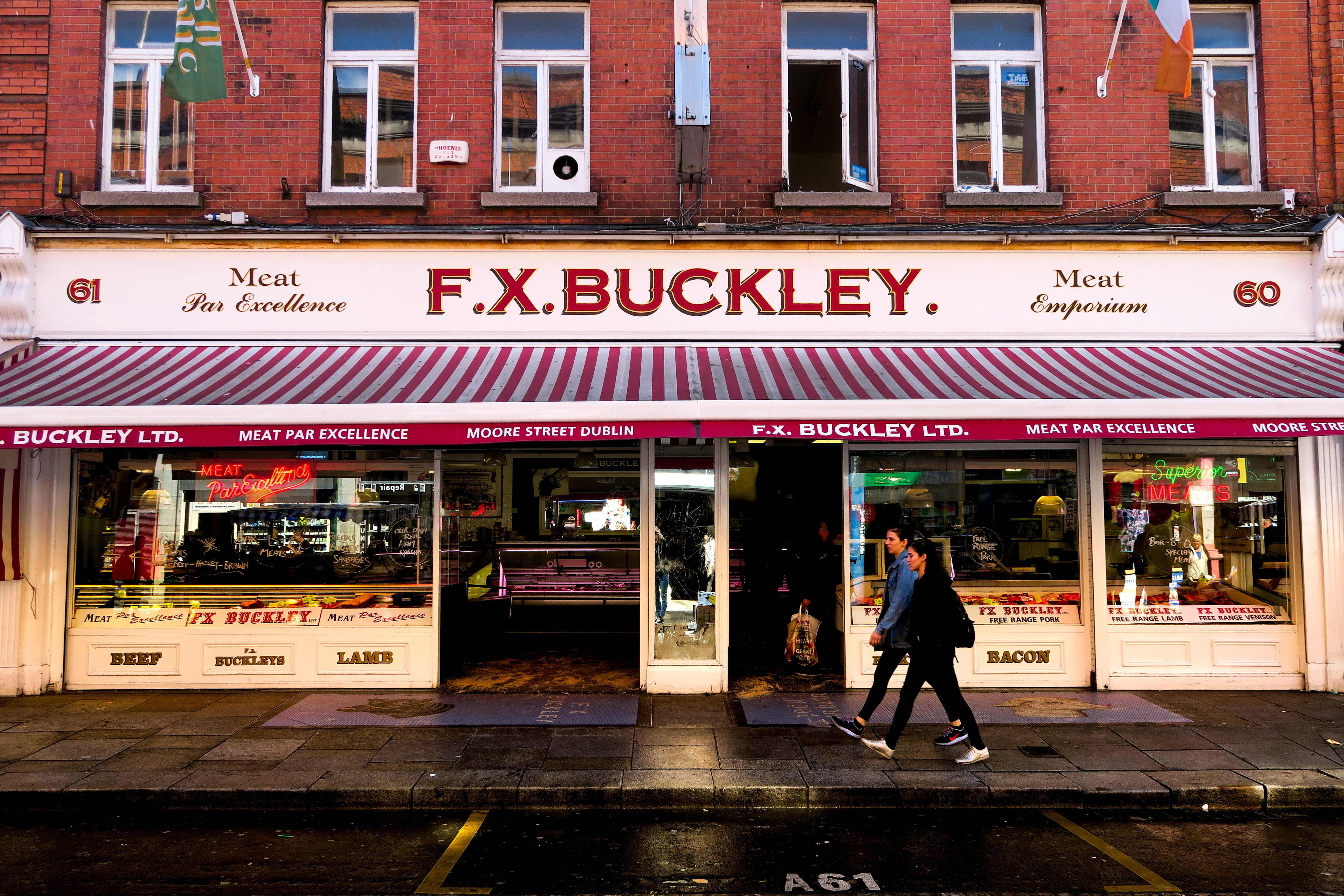 man and woman walking in front of F.X. Buckley store