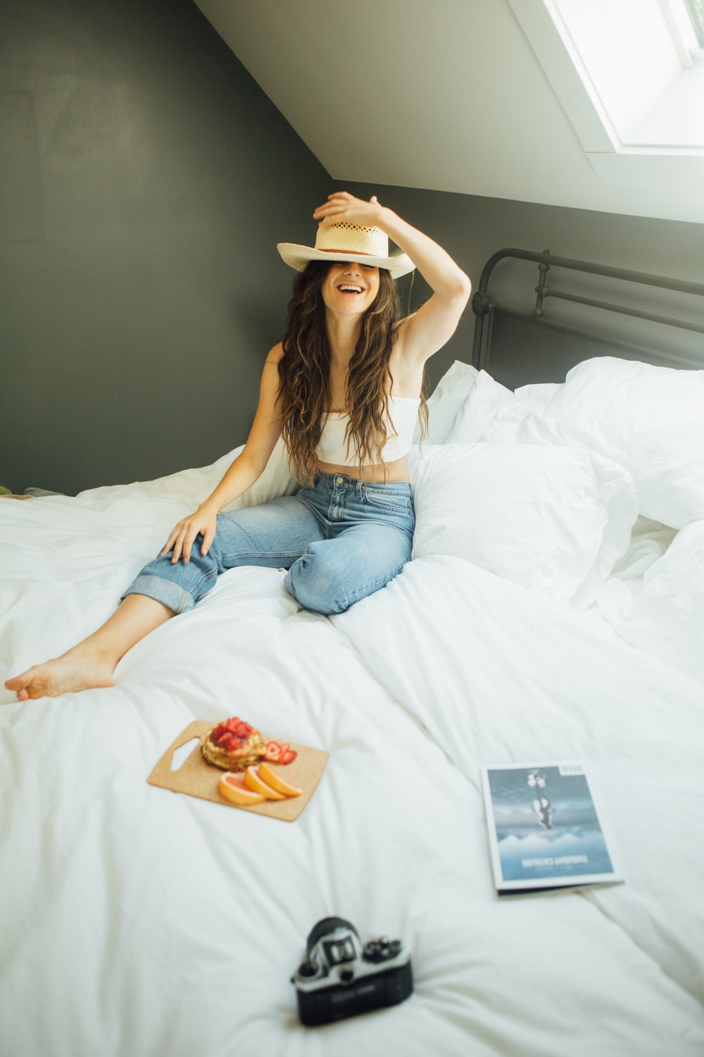 woman sitting on bed holding her hat