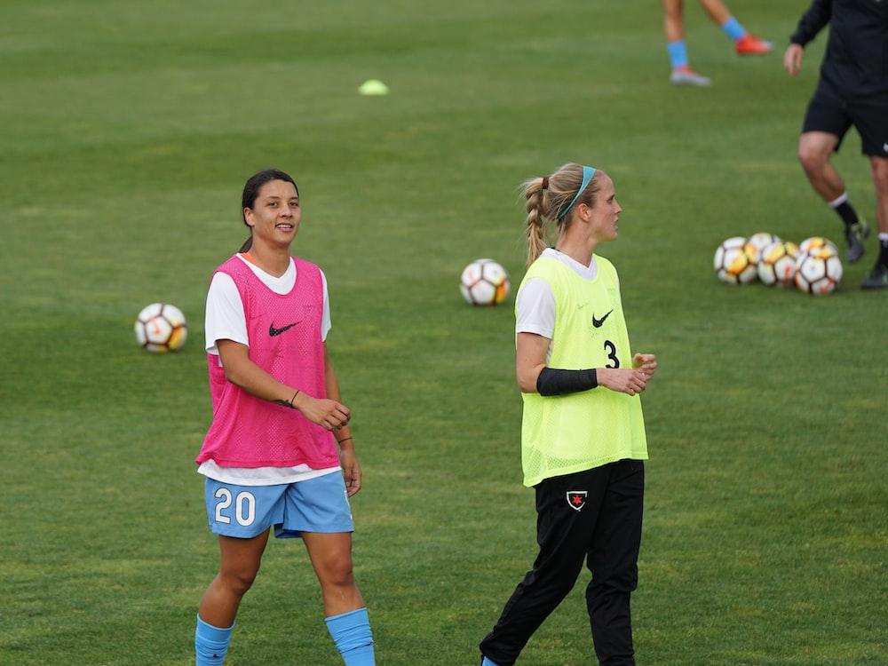 two women wearing pink and yellow Nike tank tops