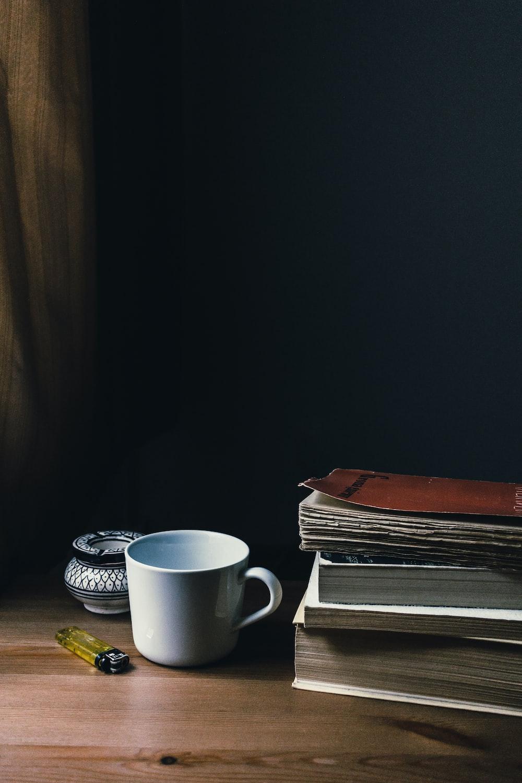 white ceramic mug beside books and disposable lighter