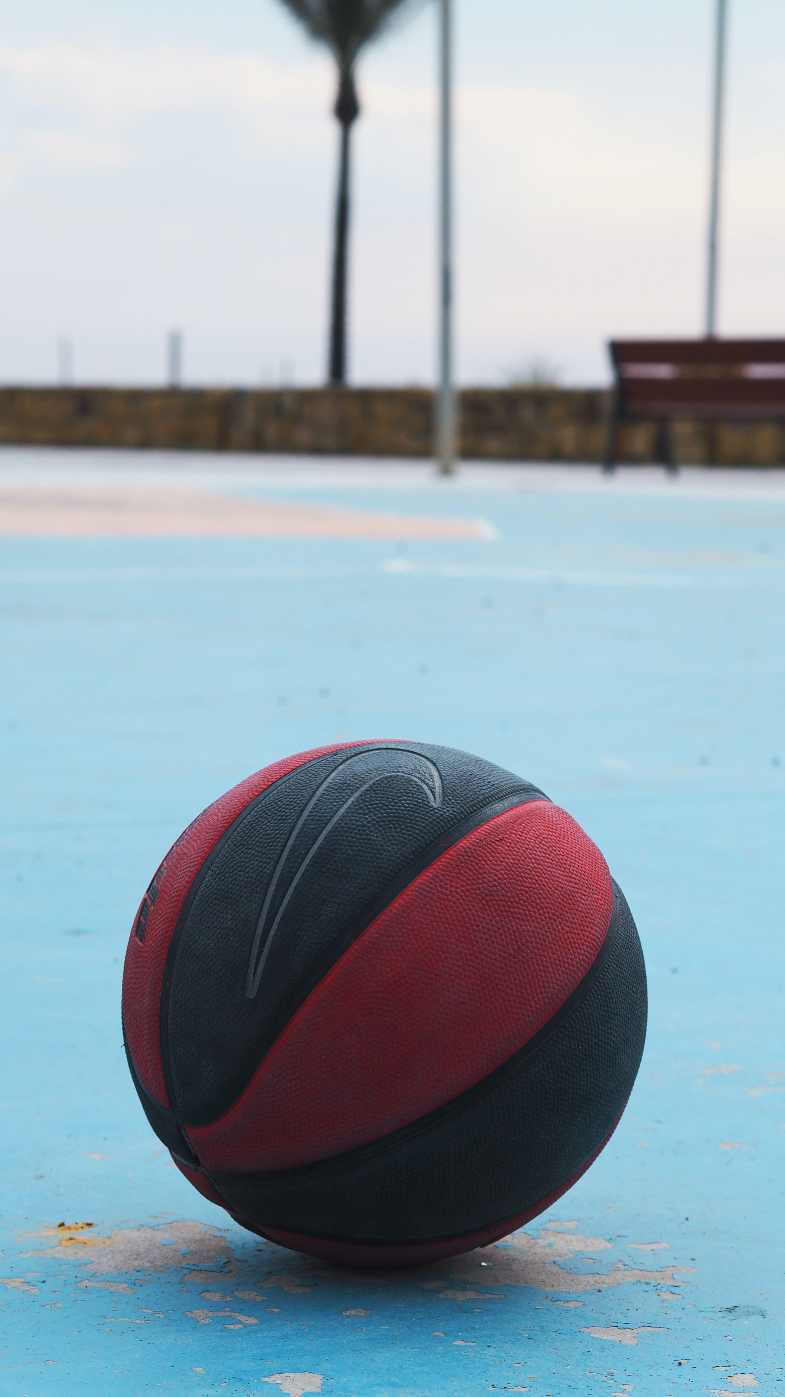 selective focus photo of red and black Nike ball on basketball court