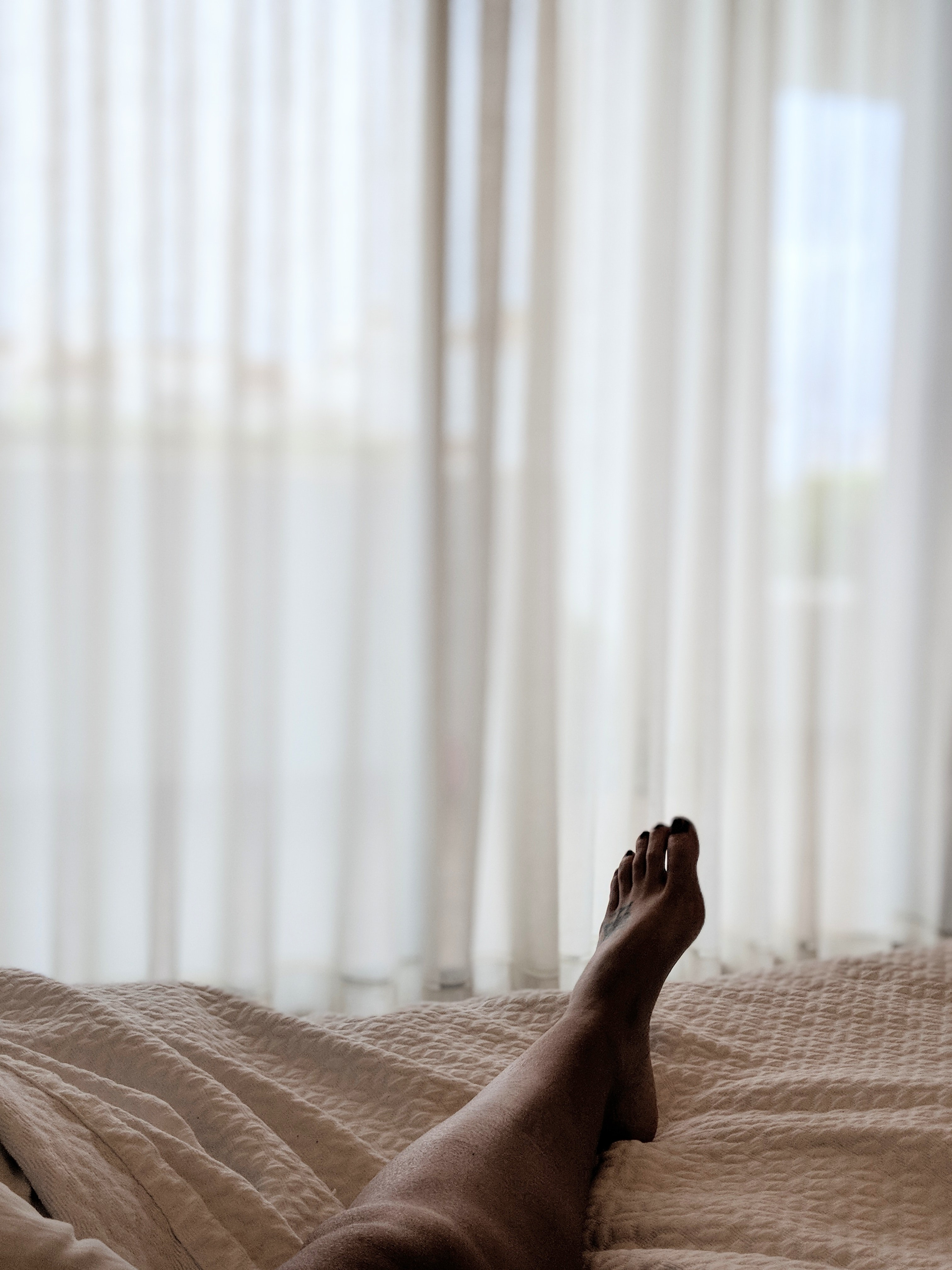 person lying on brown bed sheet