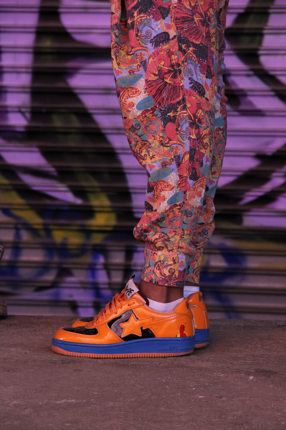person wearing orange-and-blue low-top sneakers