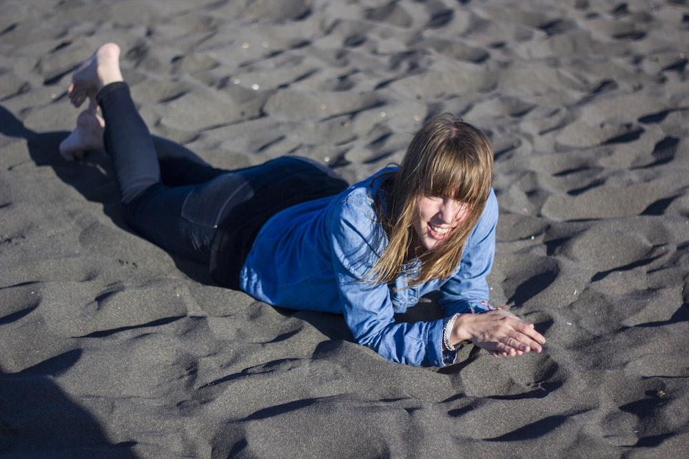 woman lying on grey sand