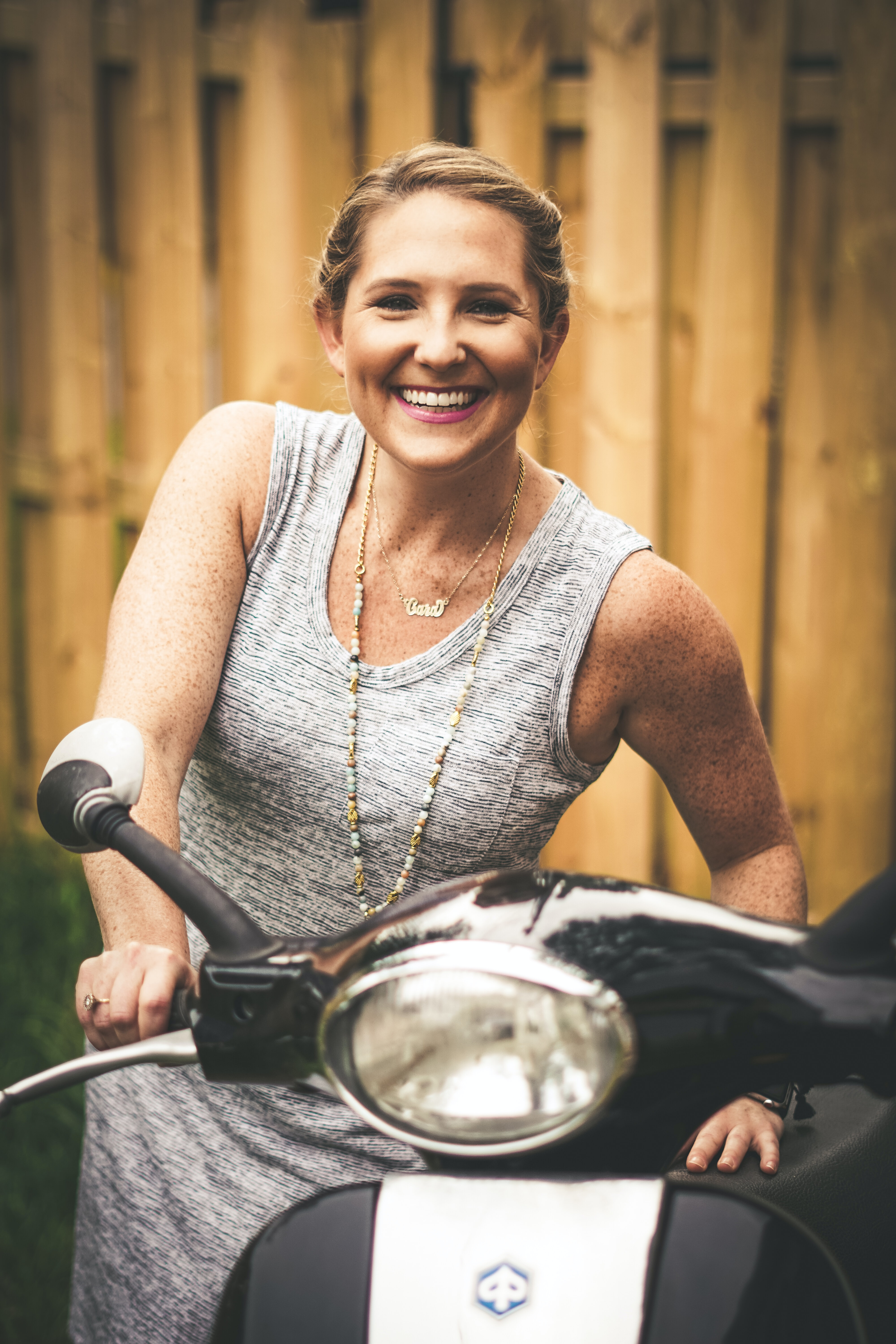 smiling woman holding black and gray motor scooter