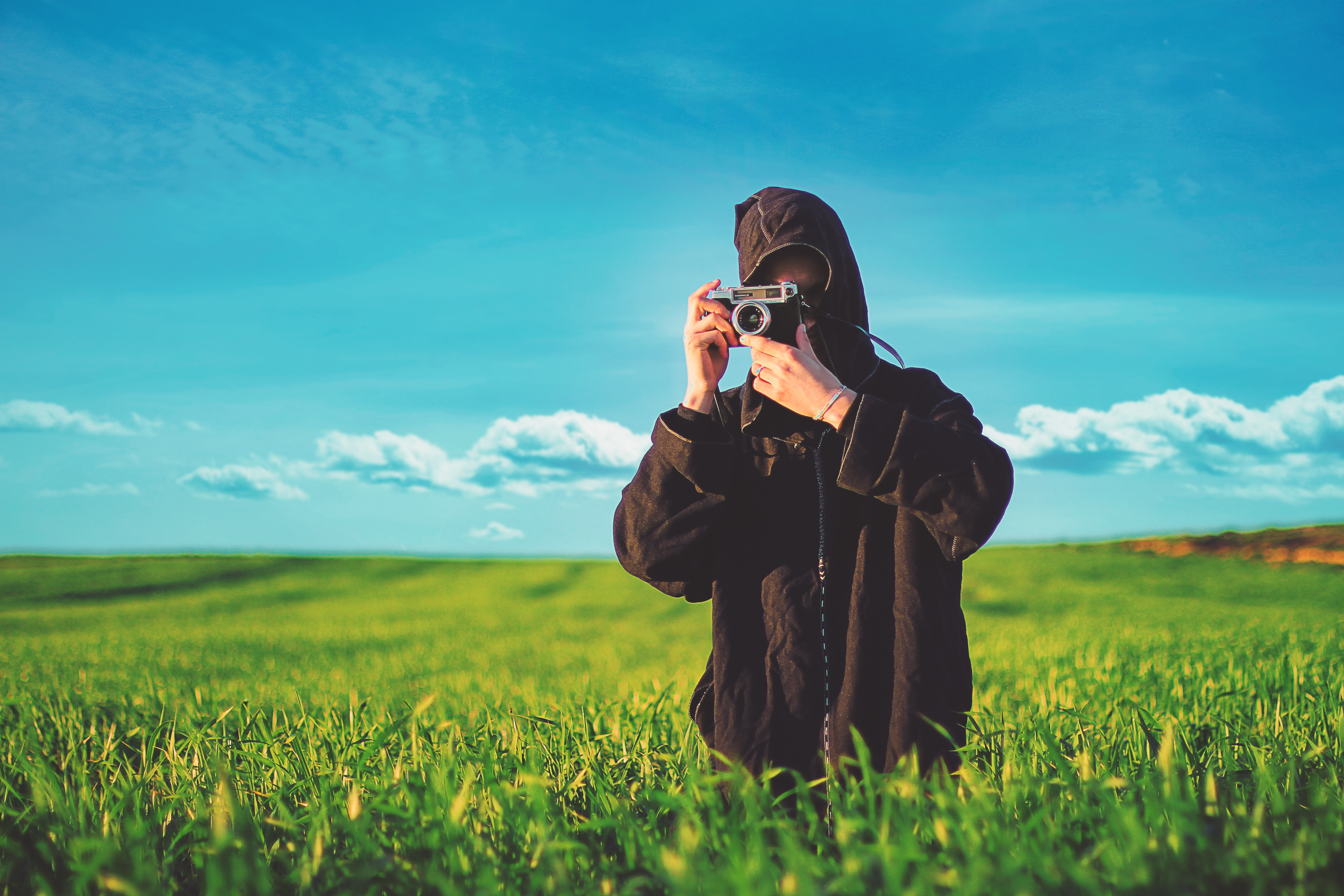 person taking photo using camera in green field