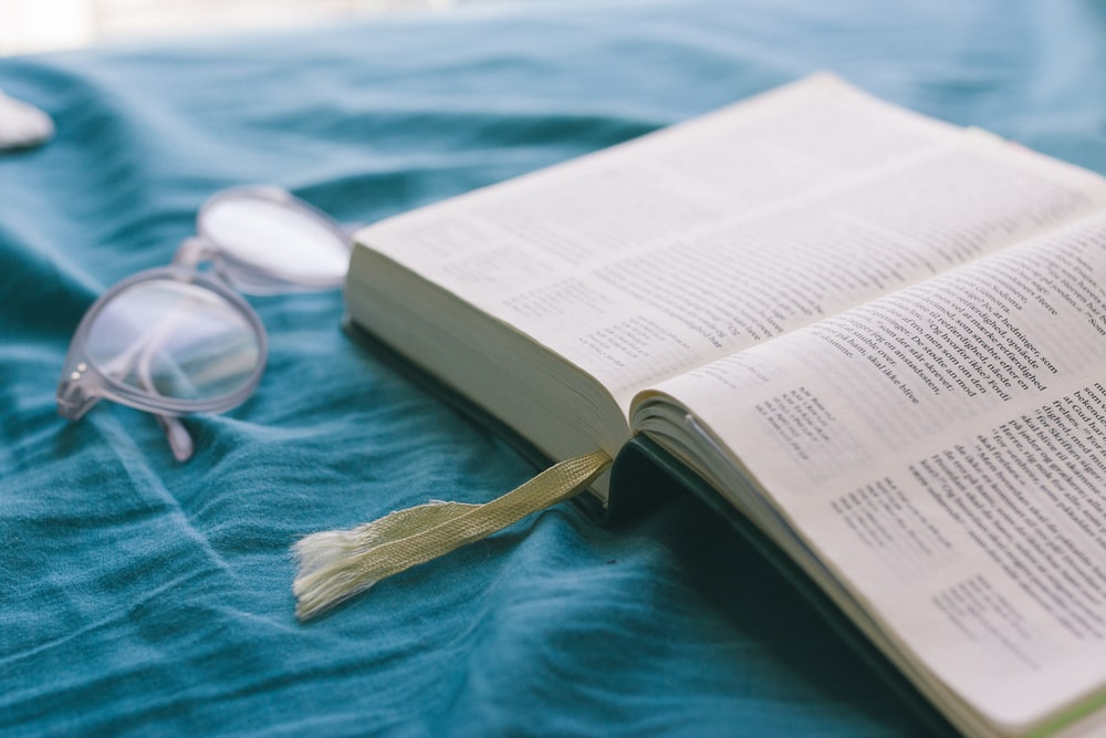 opened Bible near clear eyeglass on teal textile