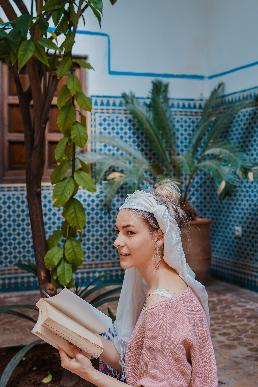 woman reading a book near tree