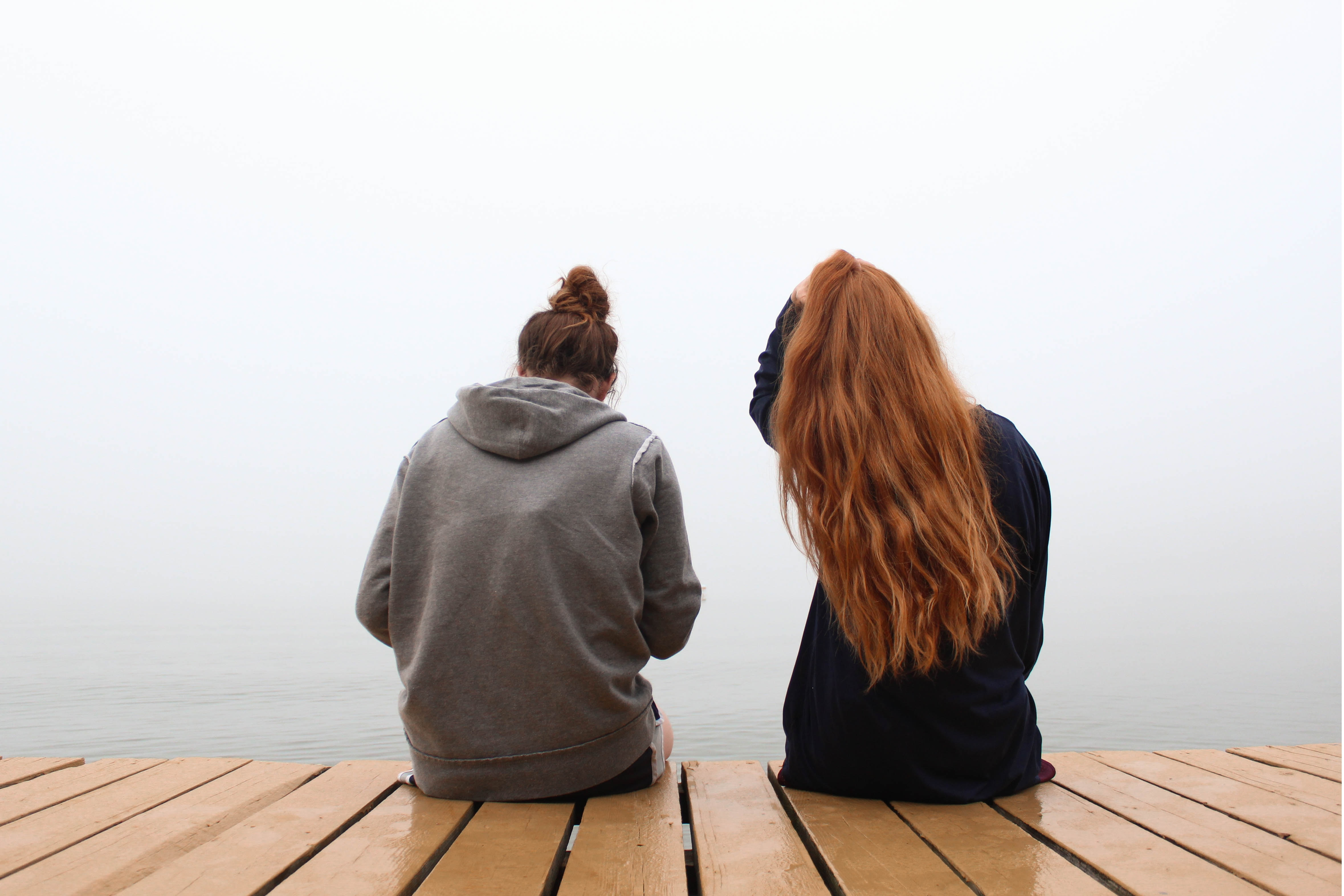 two women sitting on wooden dock over body of water