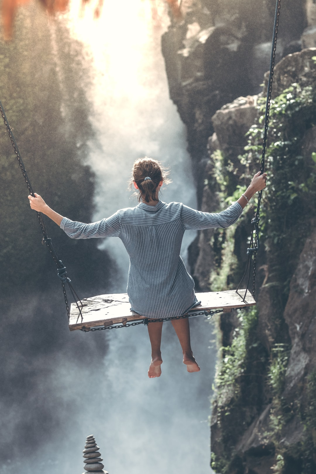 Beautiful woman swings near waterfall