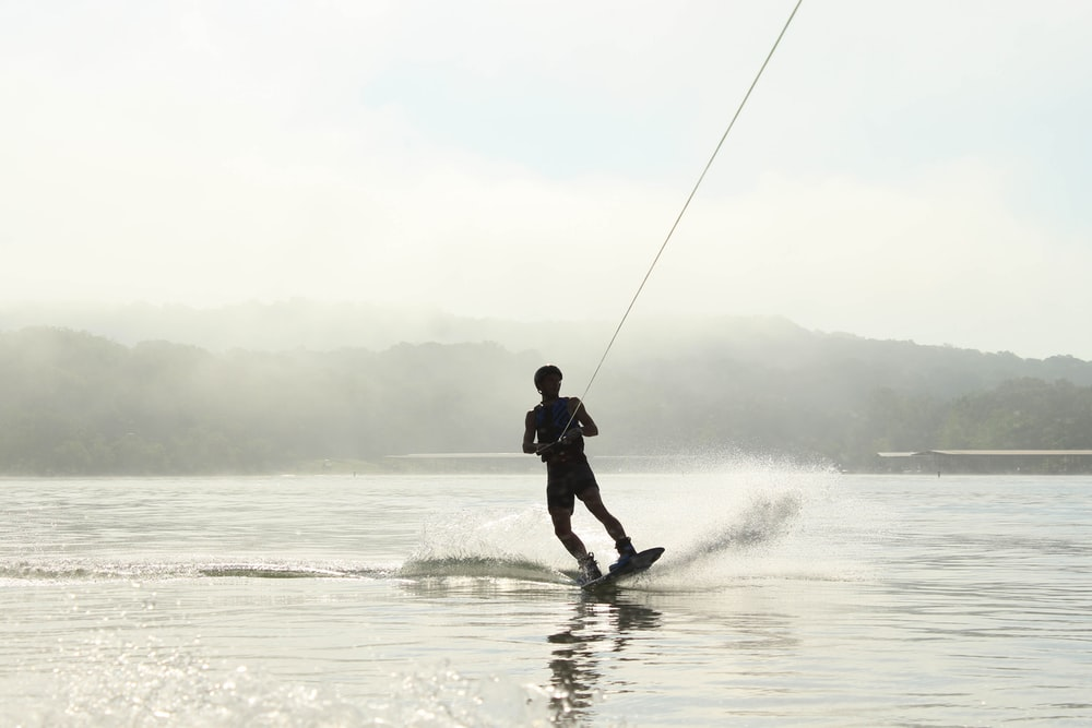 photo of man surfing on body of water and holding rope