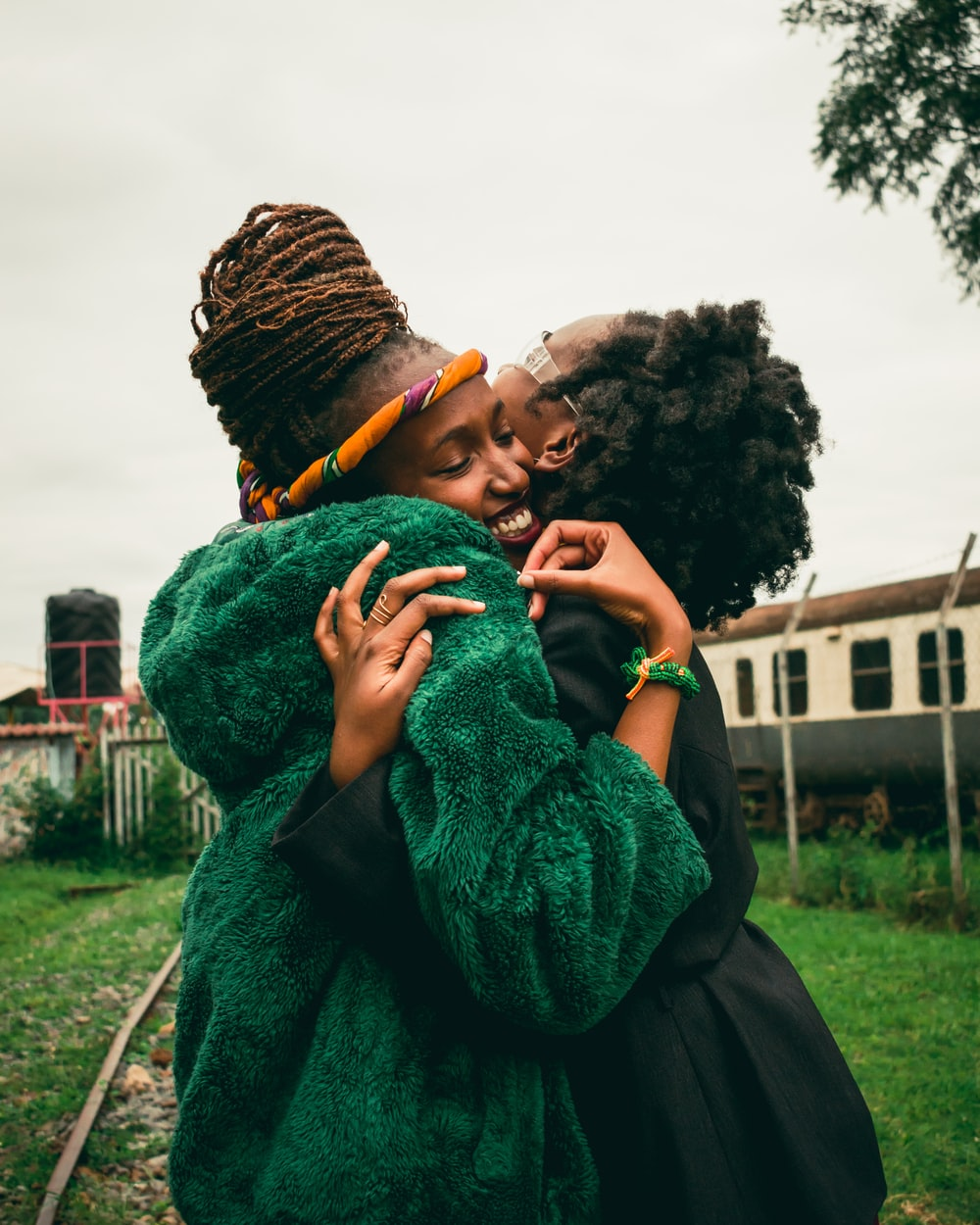 two women hugging during day time
