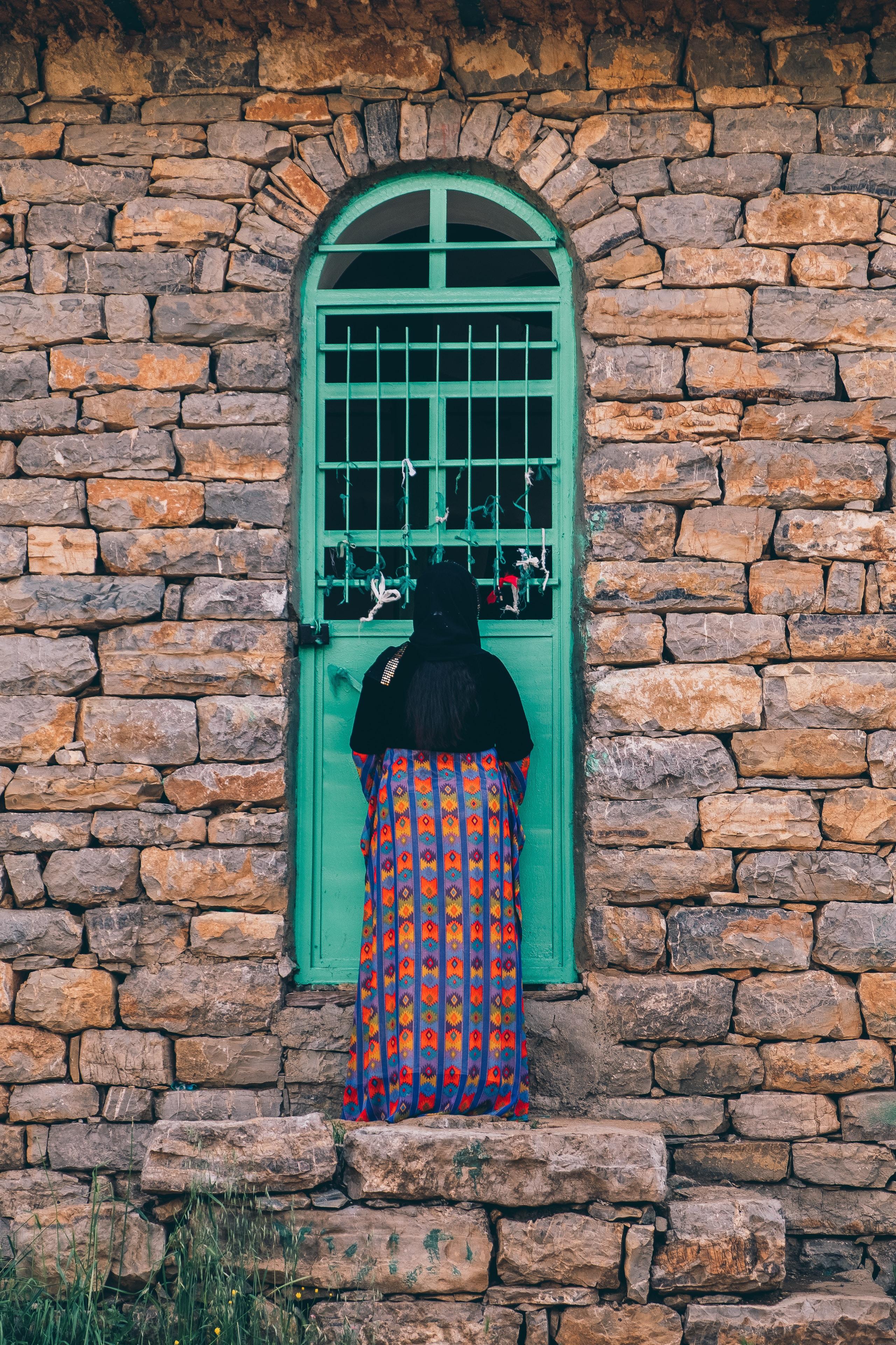 woman standing in front of green door