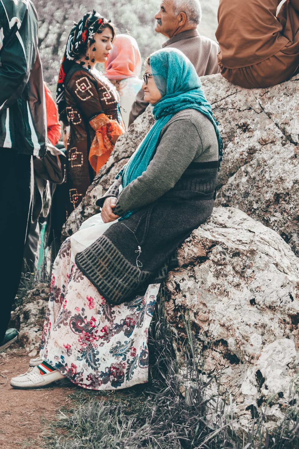 woman in grey long-sleeved shirt and teal scarf sitting on rock during daytime