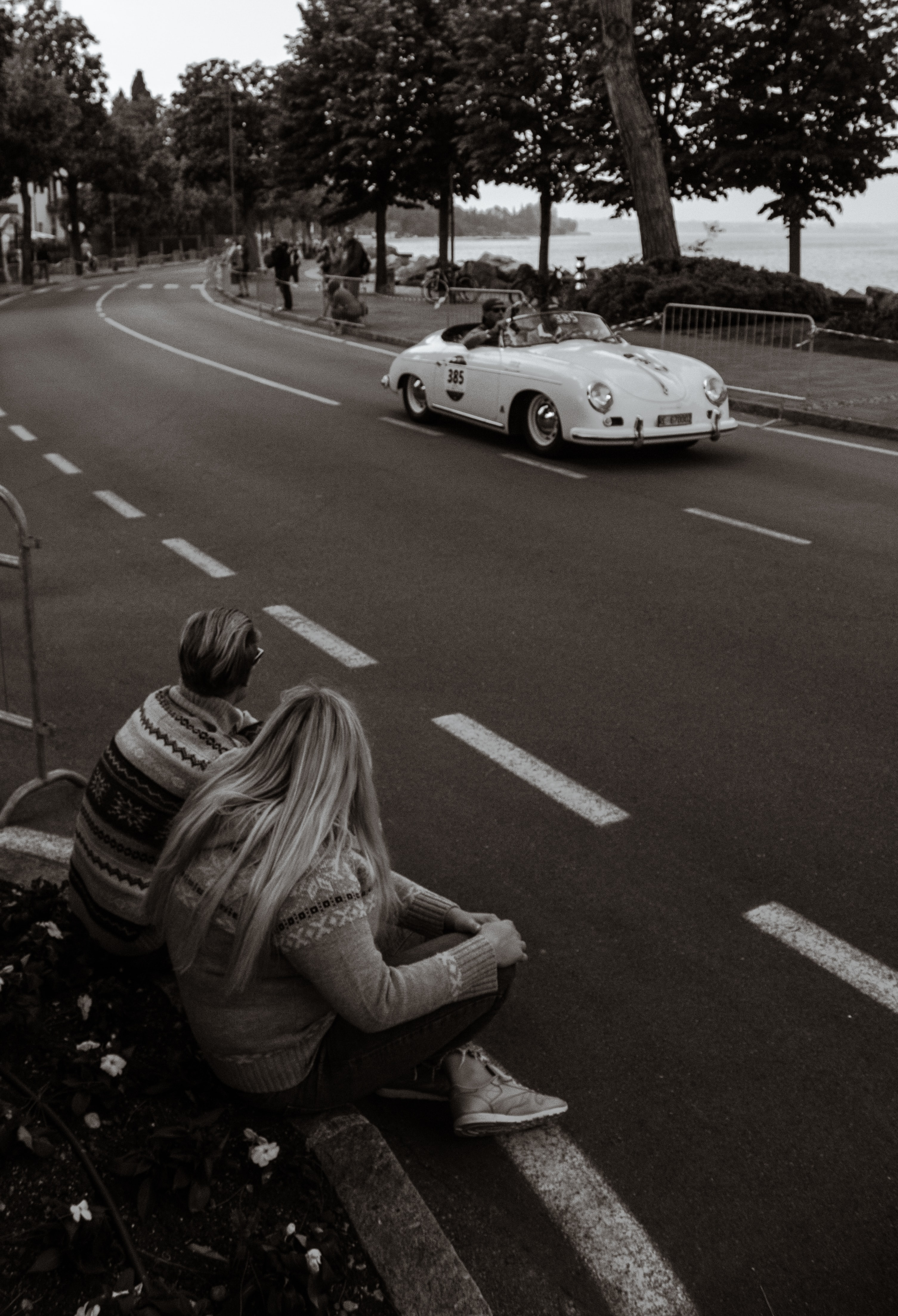 grayscale photo of man and woman sitting on street facing white coupe