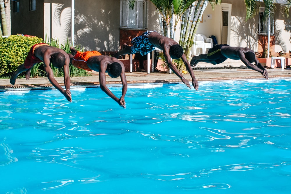 four men diving to the pool
