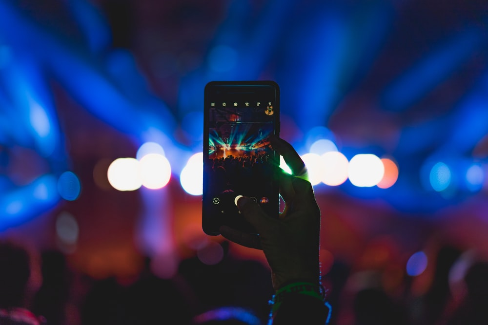 person taking photo of live concert