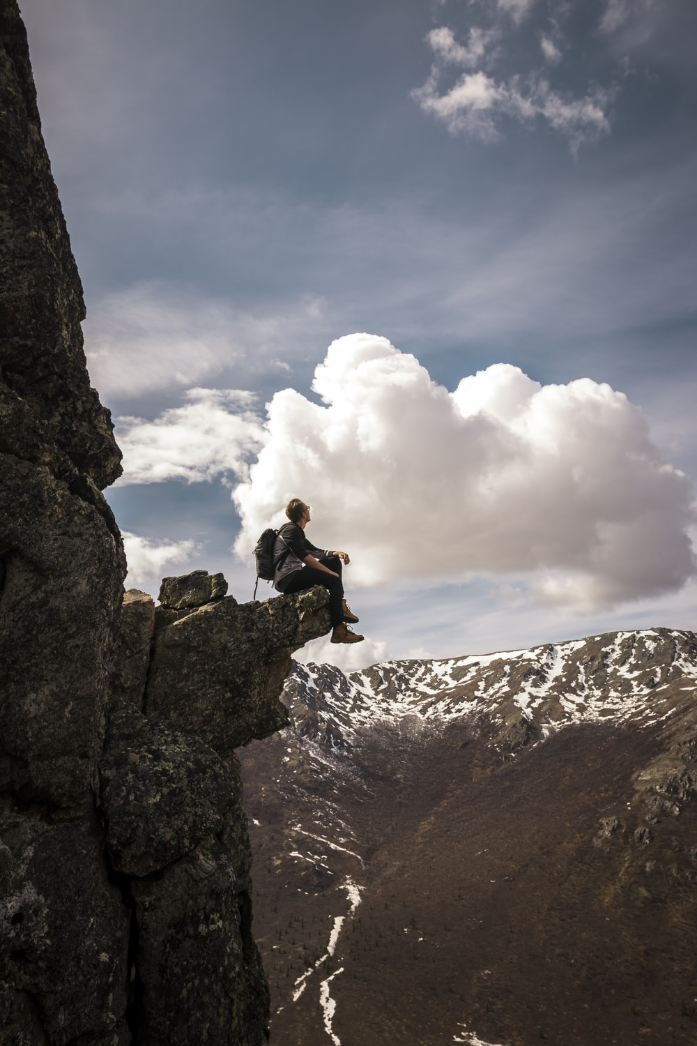 man sitting on mountain edge while looking at the sky