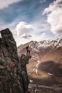 man standing on rock facing mountains