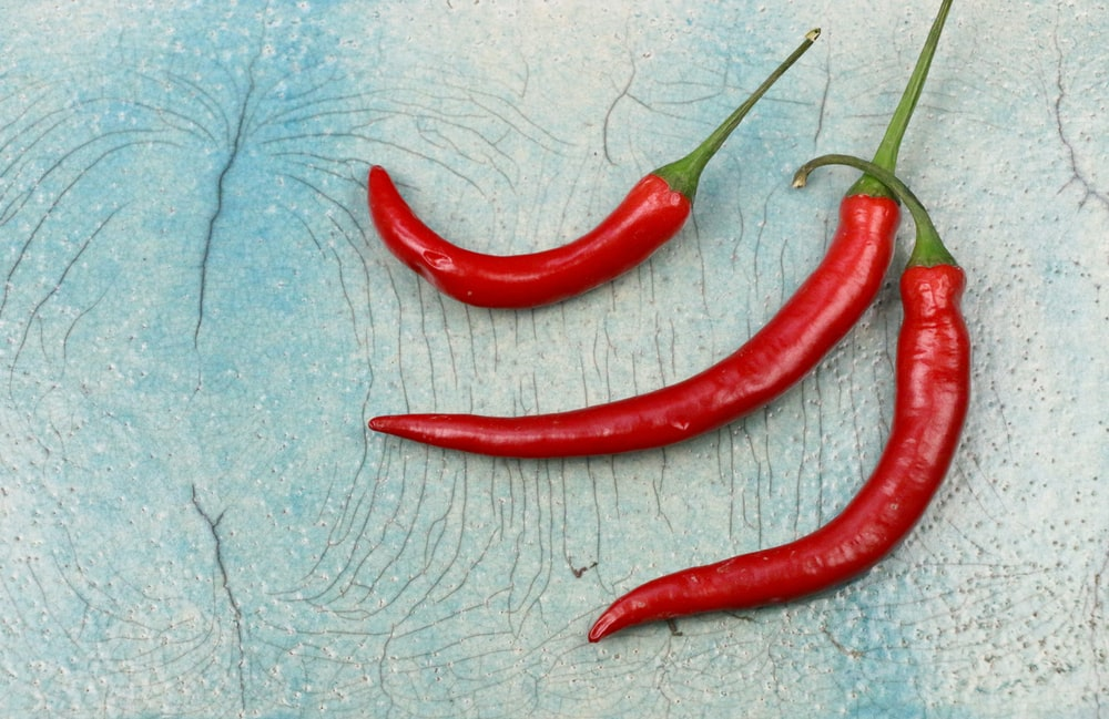 three red chili on gray surface